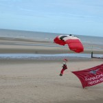 Red Devils army parachute team leader landing with flag.