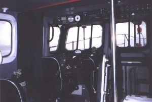 Inside wheelhouse,steering position.Door open to engine room.This is kept locked at sea,to preserve the boat's self-righting capability.Above the helmsman's position is the VHF direction-finding receiver and depth indicator.