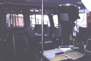 Radar and navigation positions. Radar behind upright post; GPS laser plotter to right above chart table; Yeoman plotter on chart table; GPS and Decca below plotter,