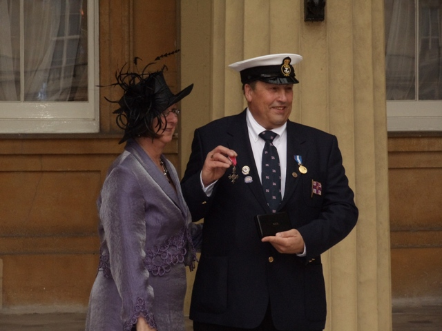 Paul and his partner Mary with the MBE outside the Palace steps