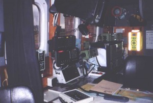 Communications radios, GPS, etc. Above chart table are mechanic's controls; GPS; Decca. To right of these is the green VHF radio. To right of this is the long-range MF radio and GMDSS selective calling sets for both VHF and MF